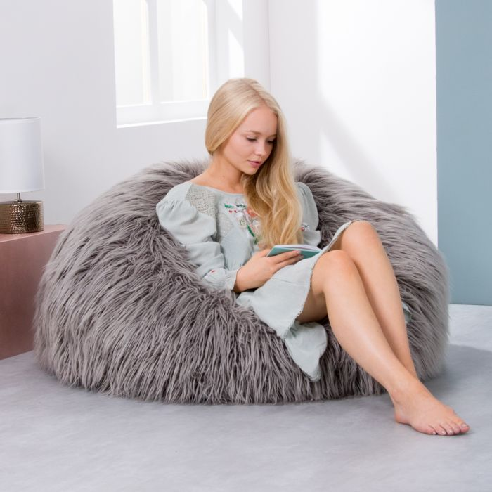 8149df8a817 girl sitting in grey mongolian shaggy faux fur bean bag in living room