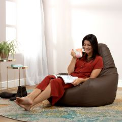 Lady sitting in faux leather brwon recliner bean bag in living room
