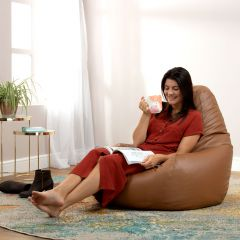 Lady sitting in faux leather tan recliner bean bag in living room